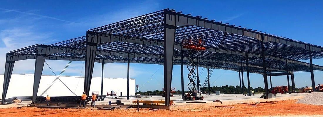 steel building being put up under blue skies