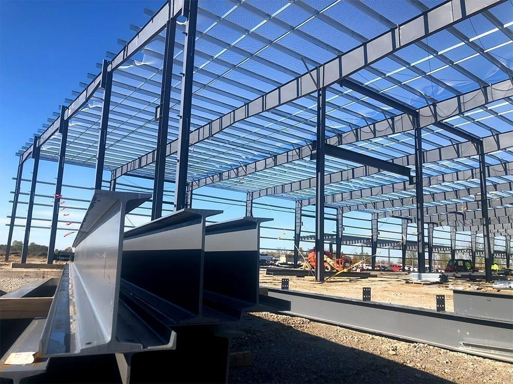 steel building erection with I-beams in the foreground